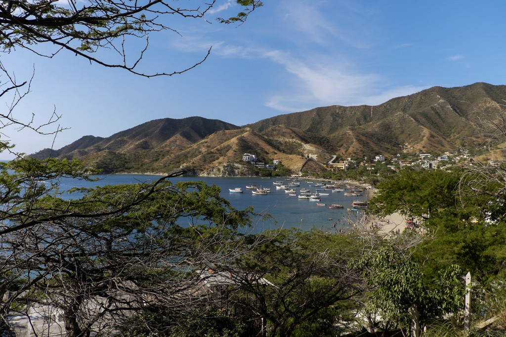 Tourists play in the cool waters among anchored fishing boats in the Caribbean town of Taganga, Colombia.